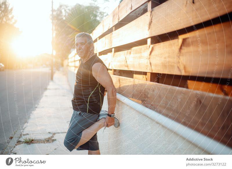 Älterer Mann streckt sich auf Holzwand in Straße strecken sportlich älter Wand reif alt Form Training Läufer Athlet Fitness Großstadt passen Gesundheit Übung