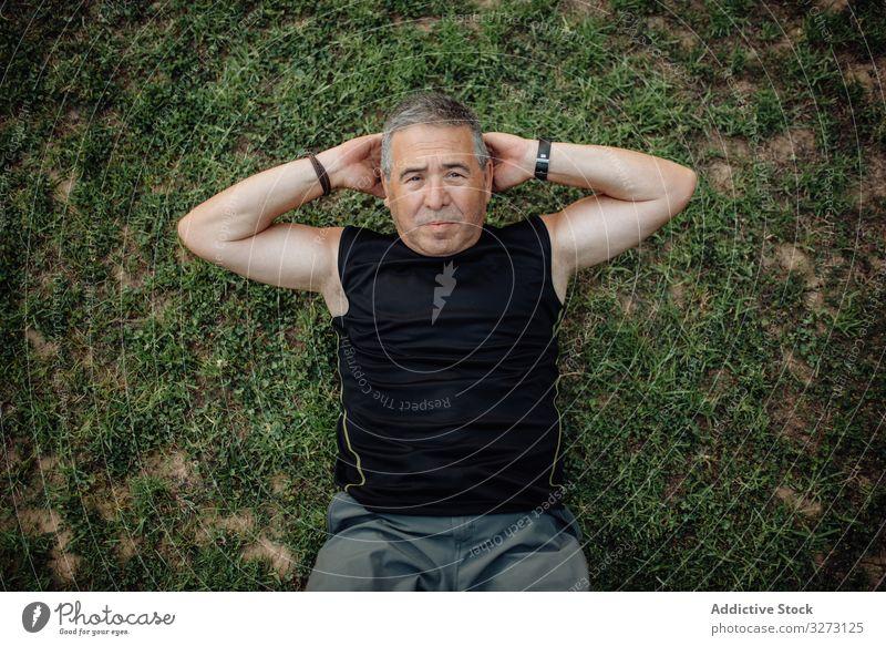 Fröhlicher älterer Mann macht Bauchmuskeln auf grünem Gras im Park nach oben drängen sportlich reif alt Form Training Athlet Fitness Großstadt passen Gesundheit