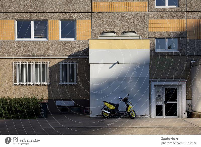 Plattenbau-Fassade mit gelbem Roller Berlin Stadt Menschenleer Haus Hochhaus Mauer Wand Fenster Tür Kleinmotorrad Stein Beton fahren Häusliches Leben eckig