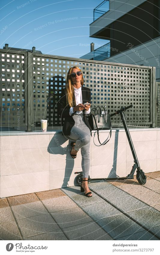 Geschäftsfrau, die ihr Handy mit ihrem Roller benutzt Lifestyle Stil schön PDA Mensch Frau Erwachsene Straße Mode Sonnenbrille sitzen warten modern attraktiv