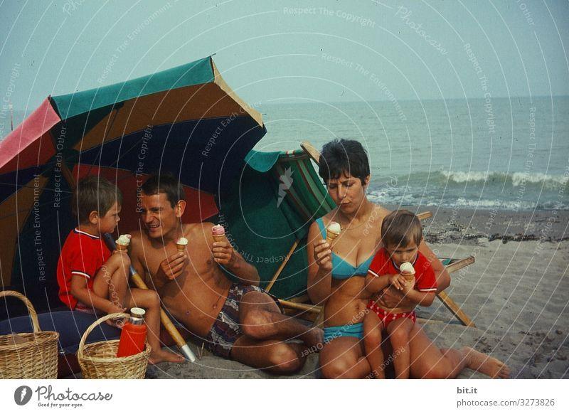 Junge, glückliche Familie sitzt in Badekleidung am Strand, unterm Sonnenschirm und macht Picknick mit Eis, in Italien am Meer, früher in den 60 er Jahren. Sie halten Waffeleis in der Hand und genießen, essen es vor dem Meer.