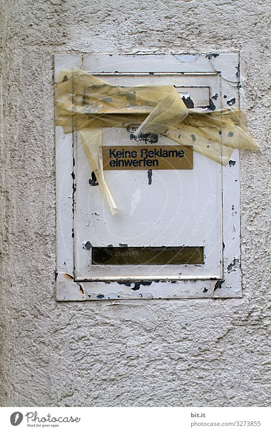 Schriftzug auf Schild: Keine Reklame einwerfen, hängt an altem, kaputten, weissen Briefkasten aus Blech, an der Wand vom Haus. Der Kasten ist mit Paketband, Tesa, Kreppband zugeklebt, verschlossen als Hinweis auf Verbot, Umzug des Mieters, Leerstand.