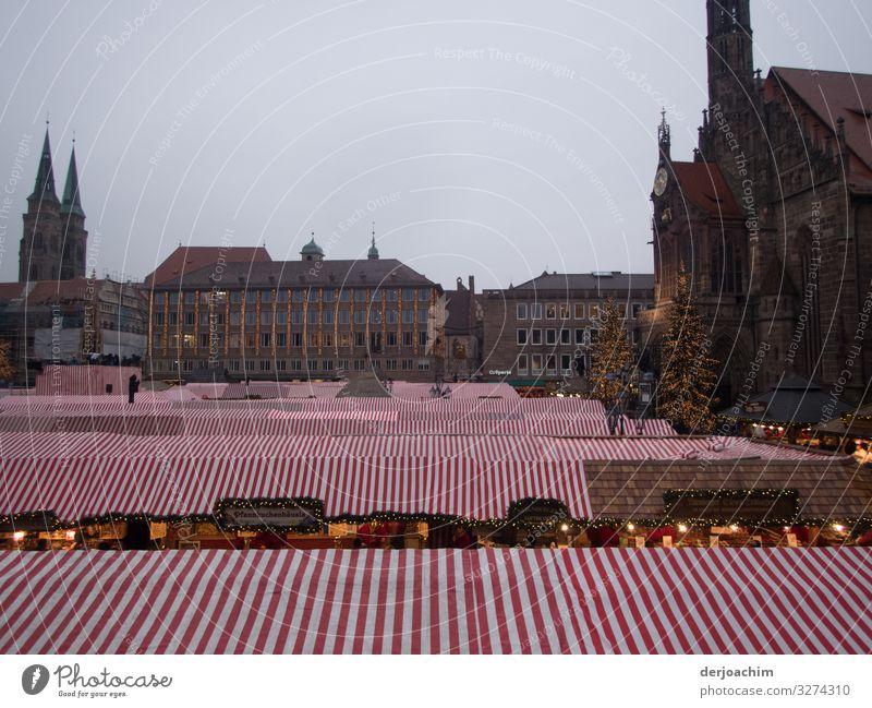 Überdacht ist der Weihnachtsmarkt in Nürnberg. . Die Stände sind mit Rot. Weiß Markisen  Überdacht. Im Hintergrund sind Fachwerkhäuser zu sehen. Freude Erholung