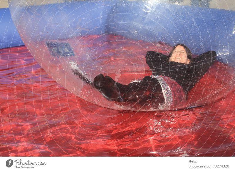 Frau liegt entspannt in einer großen Plastikkugel in einem Wasserbecken Mensch feminin Erwachsene 1 45-60 Jahre Bubble Kunststoff Kugel liegen Schwimmen & Baden