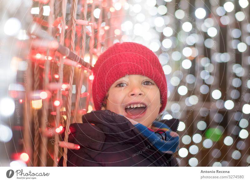 Lächelnder Junge in der Weihnachtsnacht mit Blick in die Kamera Freude Winter Feste & Feiern Kind Mensch Schal Hut weiß Gefühle Überraschung Weihnachten