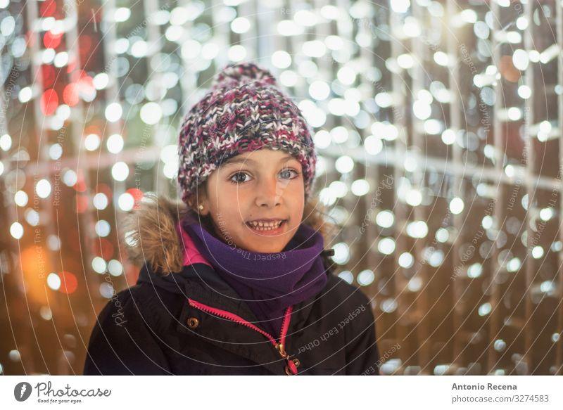 Lächelndes Mädchen mit Weihnachtslampenblitzen Lifestyle Freude Winter Dekoration & Verzierung Kind Kindheit Wärme Mantel Schal Hut lachen niedlich Gefühle
