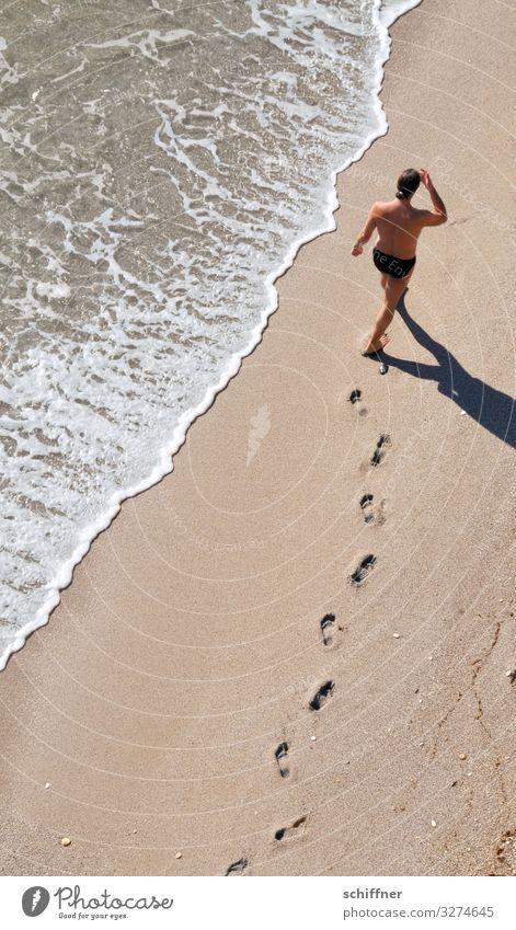 Mann läuft am Strand spazieren Urlaub Urlaubsstimmung urlaubsreif Strandspaziergang Meer Meeresufer Fußspur Barfuß Barfußstrand Meerwasser Wellen Gischt
