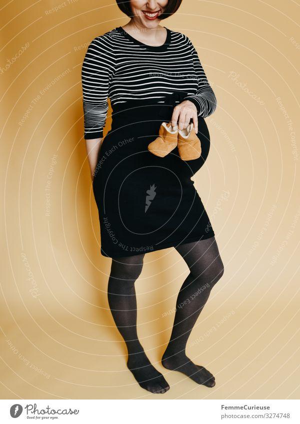Pregnant woman showing baby shoes Frau Mensch Jugendliche Freude 18-30 Jahre Erwachsene gelb feminin Glück Mode Lächeln Schuhe Baby Kleid schwanger Vorfreude