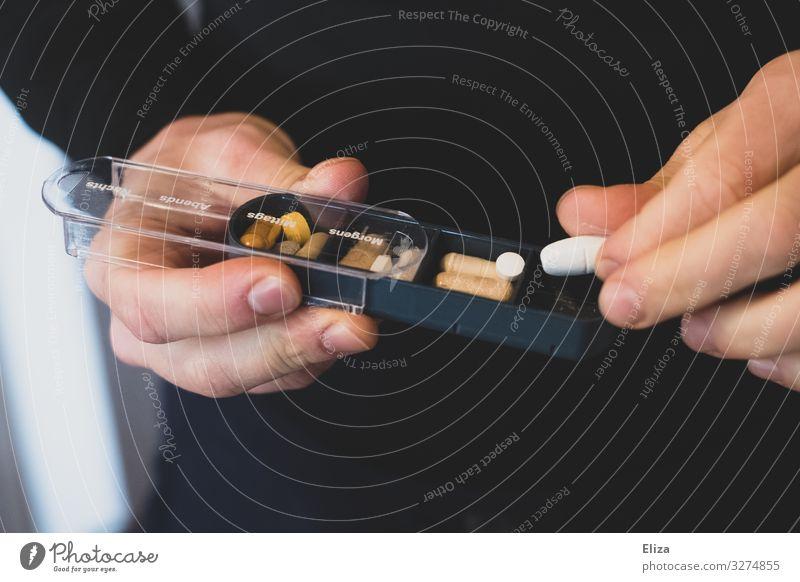 Hände die einen Tablettenbox mit Pillen und Nahrungsergänzungsmitteln halten und eine Tablette herausnehmen Gesundheit Gesundheitswesen Gesunde Ernährung