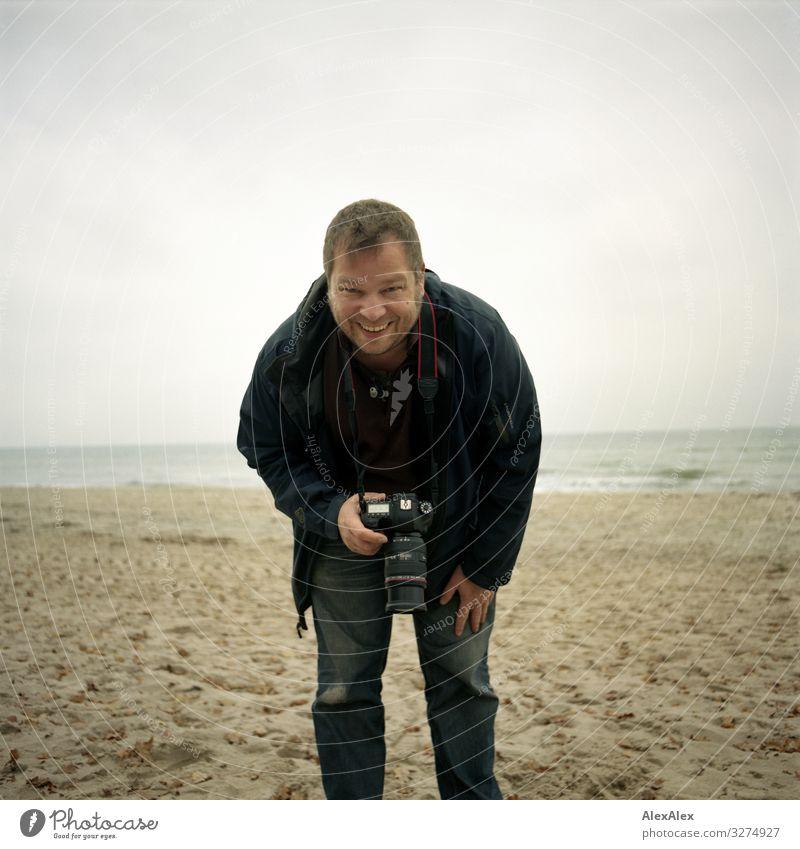 Fotograf am Ostseestrand Lifestyle Freude Ausflug Abenteuer Fotokamera Mann Erwachsene 30-45 Jahre Landschaft Herbst Strand Jeanshose Jacke blond kurzhaarig
