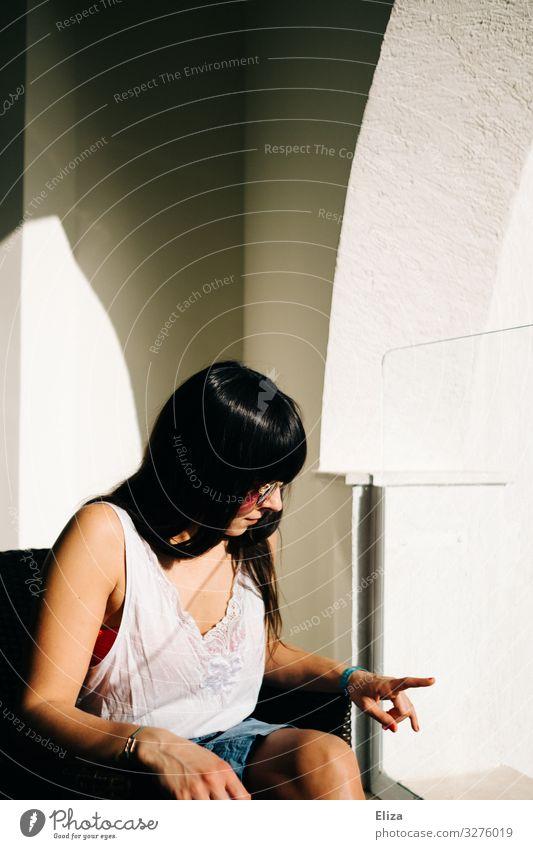 Eine Frau die Zuhause in der Sonne auf dem Balkon sitzt und gelangweilt ihren Finger begutachtet feminin Junge Frau Jugendliche Erwachsene 18-30 Jahre