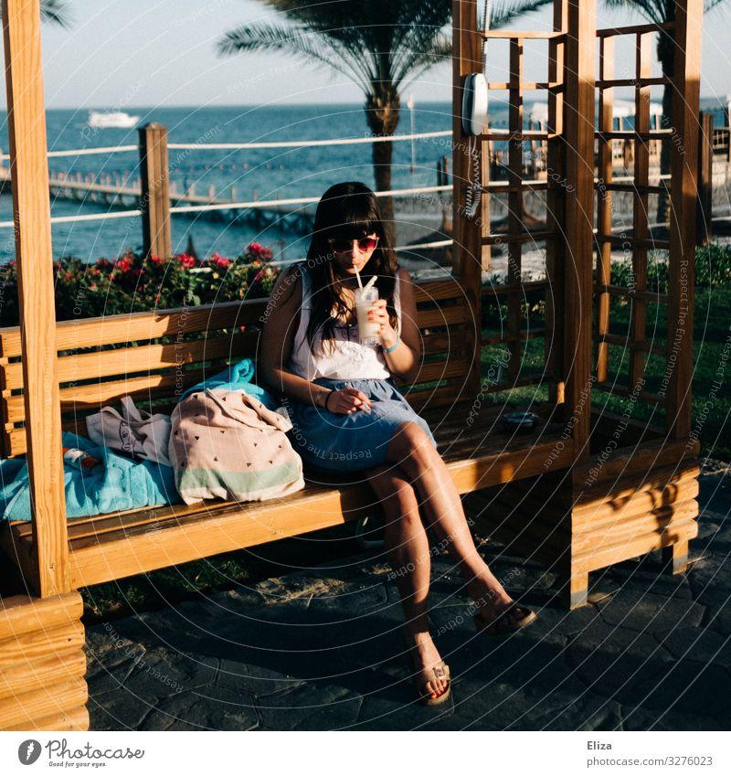 Eine junge Frau die im Urlaub am Meer auf einer Bank in der Sonne sitzt und ein Getränk trinkt feminin Junge Frau Jugendliche Erwachsene 18-30 Jahre