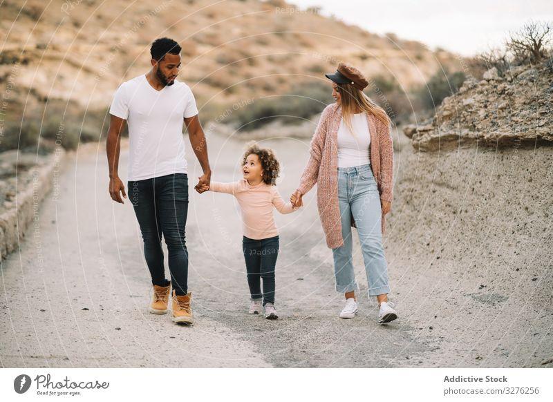 Stilvolle multiethnische Familie geht in der Natur spazieren Spaziergang Hand in Hand Zusammensein Eltern Kleinkind ruhen Lächeln Glück schlendern heiter