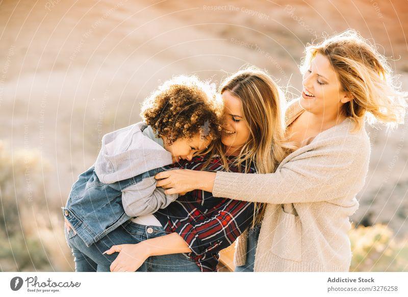 Lächelnde blonde Frauen mit lockigem Kind Kleinkind Spaziergang Spaß Natur spielen ruhen Glück heiter Lifestyle modern Bonden Liebe Angebot lässig Unschuld