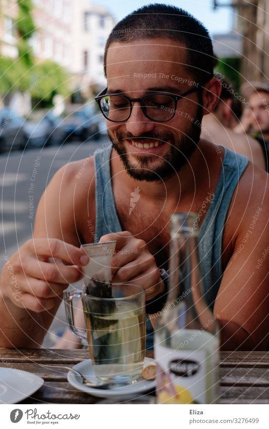 Ein Mann der draußen im Sommer in einem Café sitzt und einen Tee trinkt und lächelt Mensch maskulin Junger Mann Jugendliche Erwachsene Lächeln Außenaufnahme