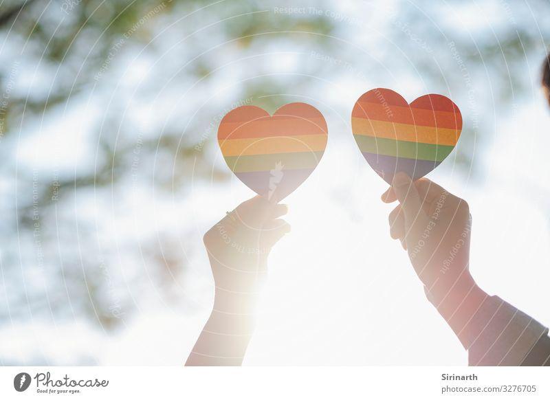 Nahaufnahme eines LGBTQ-Paares, das ein Regenbogenherz hält. Homosexualität Familie & Verwandtschaft Liebe lgbt lgbtq Geschlecht geschlechtliche Identität Stolz