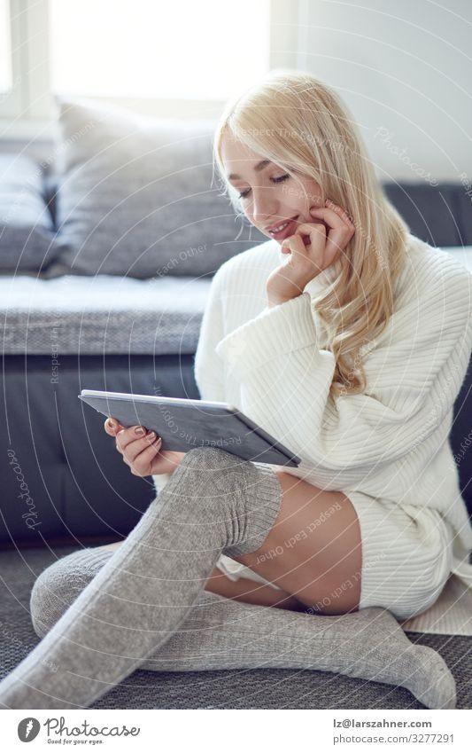 Trendige lächelnde blonde Frau in Winter-Leggings Gesicht Erholung lesen Wohnung Sofa Wohnzimmer Erwachsene 1 Mensch 18-30 Jahre Jugendliche Pullover Lächeln