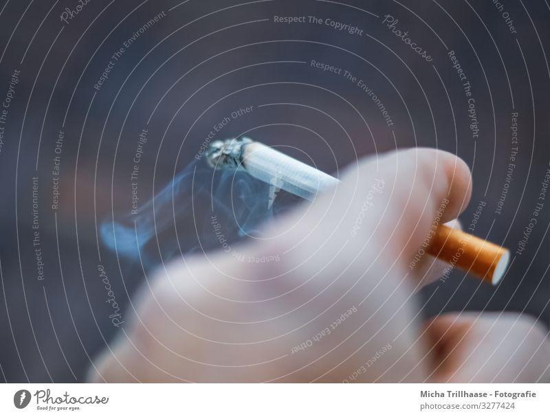 Brennende Zigarette in der Hand Gesundheit Gesundheitswesen Behandlung Krankheit Rauchen Finger nah blau gelb orange schwarz Laster Willensstärke Sucht