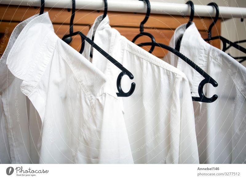 Reihe von weißen Baumwollkleidern hängen an schwarzen Bügeln auf einem Gestell kaufen Stil Design Büro Business Frau Erwachsene Mann Mode Bekleidung T-Shirt