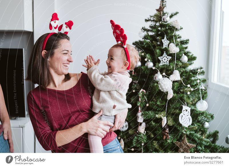 Mutter und süßes Mädchen spielen zu Hause mit dem Rentierdiadem. Weihnachts-Konzept Spielen Diadem Weihnachtsmann Mutterschaft Glück niedlich Baby ein Jahr