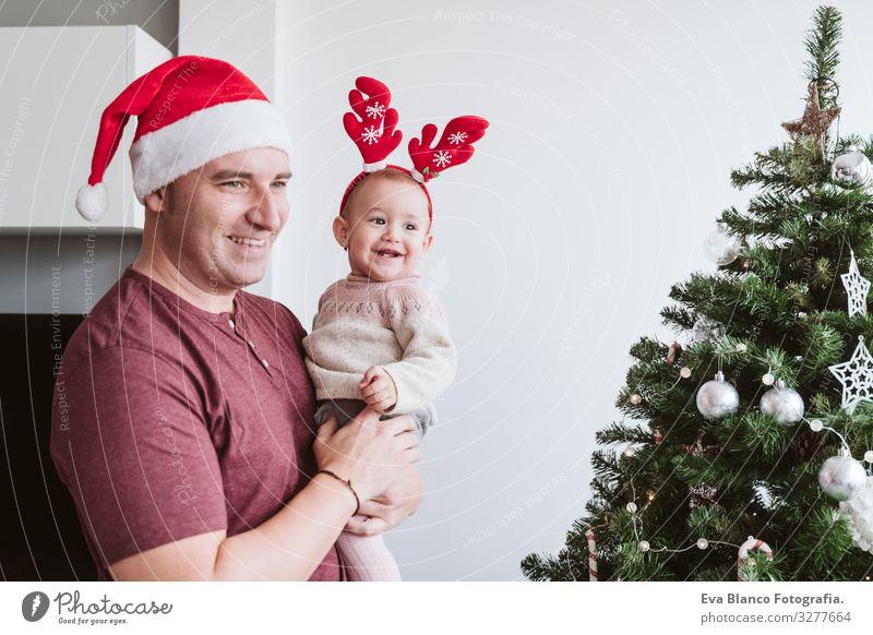 Glücklicher Vater mit Mädchen spielt zu Hause mit Rentierdiadem. Weihnachts-Konzept Eltern Elternschaft Lächeln Halt Spielen Diadem Weihnachtsmann Mutter