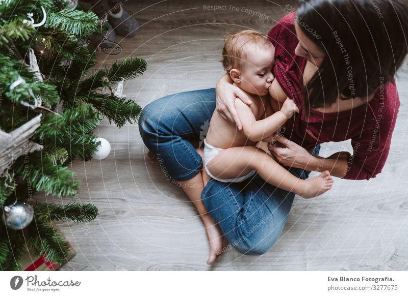 Mutter, die ihr Kind am Weihnachtsbaum stillt stillen Fressen Essen natürlich Lebensmittel Mutterschaft Glück niedlich Baby Mädchen ein Jahr dekorierend