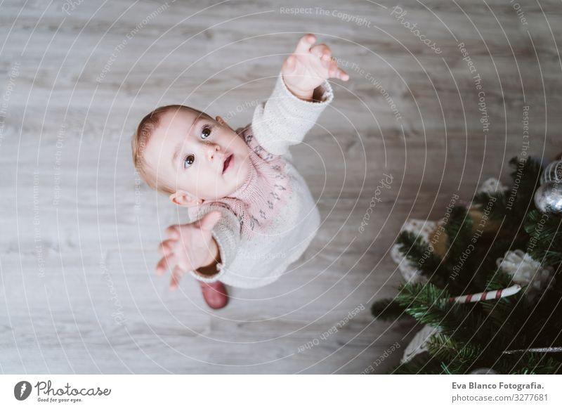 süßes Mädchen schmückt den Weihnachtsbaum niedlich Baby ein Jahr dekorierend Weihnachten & Advent Baum Freude Familie & Verwandtschaft Liebe