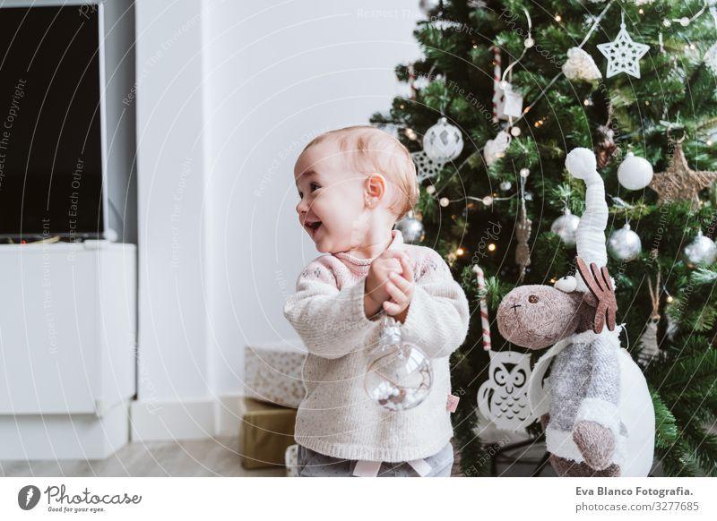 fröhliches kleines Mädchen beim Schmücken des Weihnachtsbaums Glück niedlich Baby ein Jahr dekorierend Weihnachten & Advent Baum Freude Familie & Verwandtschaft