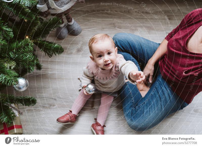 glückliche Mutter und Mädchen, die den Weihnachtsbaum schmücken Mutterschaft Glück niedlich Baby ein Jahr dekorierend Weihnachten & Advent Baum Freude