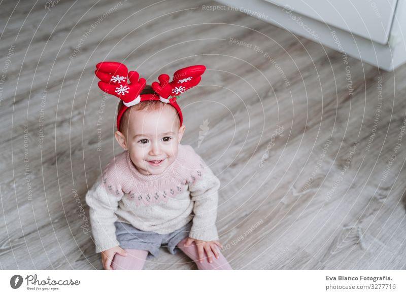 ein fröhliches Mädchen, das zu Hause mit dem Rentierdiadem spielt. Weihnachts-Konzept Spielen Diadem Weihnachtsmann Mutter Mutterschaft Glück niedlich Baby