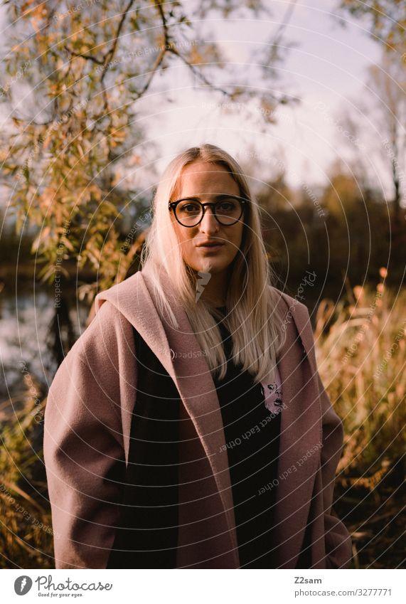 L Lifestyle elegant Stil Junge Frau Jugendliche 18-30 Jahre Erwachsene Natur Sonne Herbst Schönes Wetter Sträucher Park Mantel Brille blond langhaarig Blick
