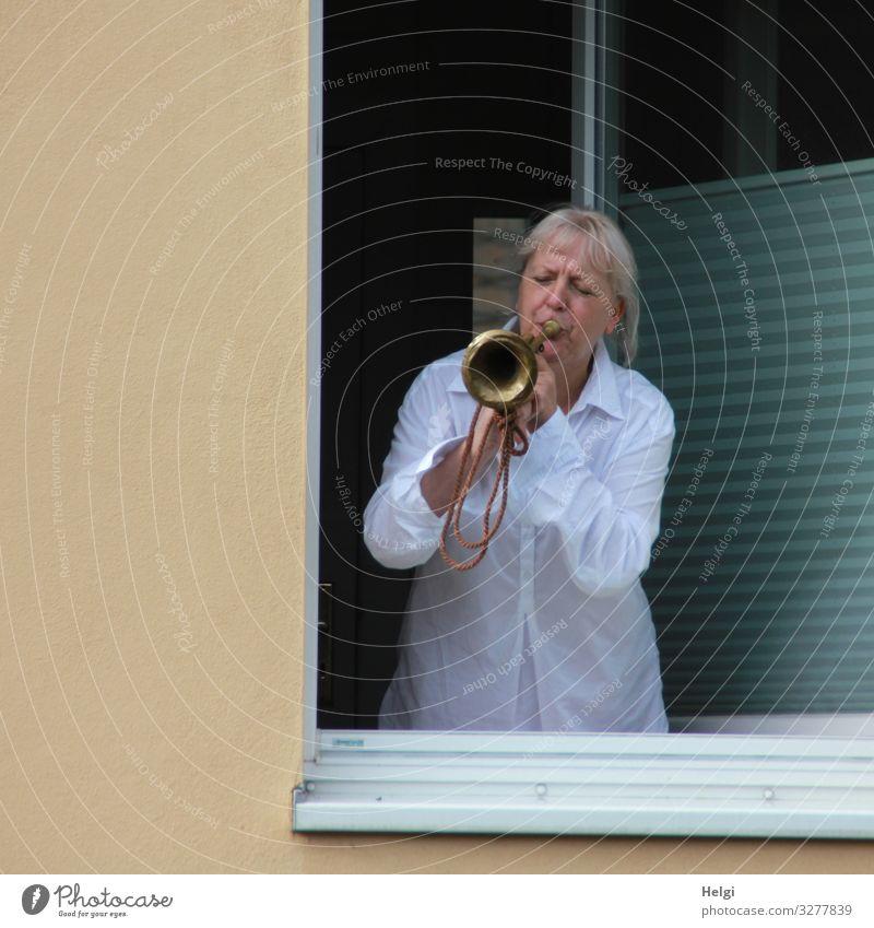 Frau steht am geöffneten Fenster und bläst in eine Trompete Mensch feminin Erwachsene Weiblicher Senior 1 45-60 Jahre Mauer Wand Bekleidung Hemd blond