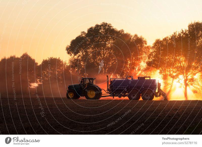 Traktor düngt landwirtschaftliches Feld bei Sonnenuntergang. Landwirtschaft Arbeit & Erwerbstätigkeit Beruf Natur Landschaft Erde orange Deutschland Aktion