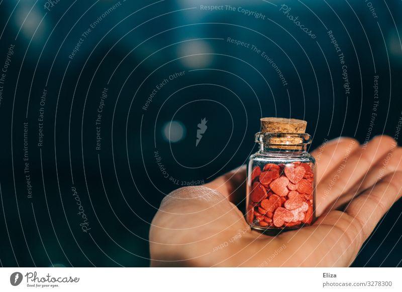Viele kleine rote Herzen gesammelt in einem Glasbehälter Apothekerfläschchen mit Korken gehalten von einer Hand; Konzept Liebe, Gefühle, verliebt Verliebtheit