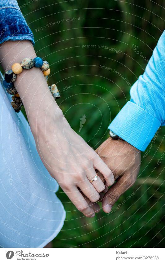 Ein Paar hält sich an der Hand mit Verlobungsring und Blauer Kleidung paar zusammen hand halten hochzeit leute frau braut ehepaar trauung aufstehen weiß liebe