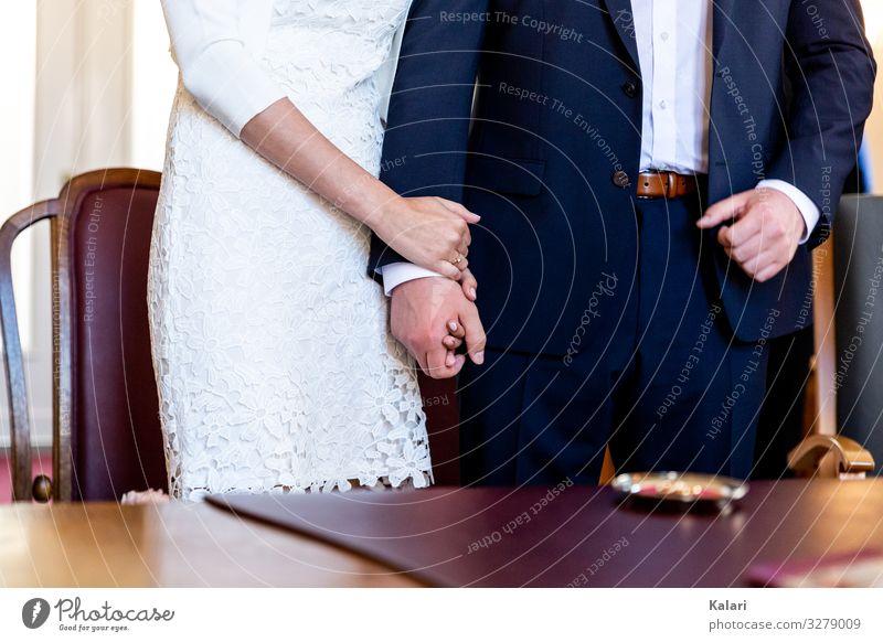Brautpaar steht während der Trauung und hält sich an der Hand hochzeit hand halten aufstehen frau händchenhalten braut ehepaar trauung weiß liebe erfolg