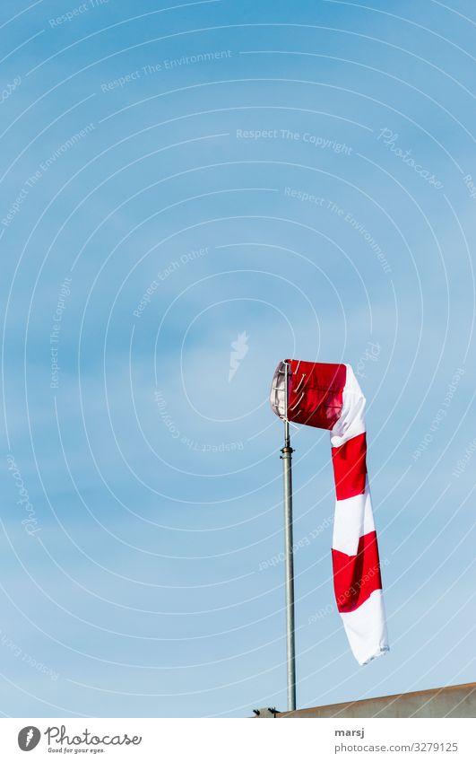 Schlaffer Windsack vor blauem Himmel Schwache Tiefenschärfe Kontrast Licht Tag Hintergrund neutral Freisteller Textfreiraum oben Menschenleer Außenaufnahme
