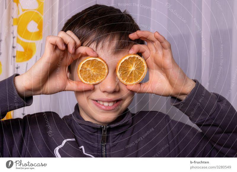 Kind mit Orangenscheiben Junge Gesicht Hand 1 Mensch 8-13 Jahre Kindheit Brille gebrauchen berühren festhalten Lächeln lachen Blick Spielen Fröhlichkeit Freude