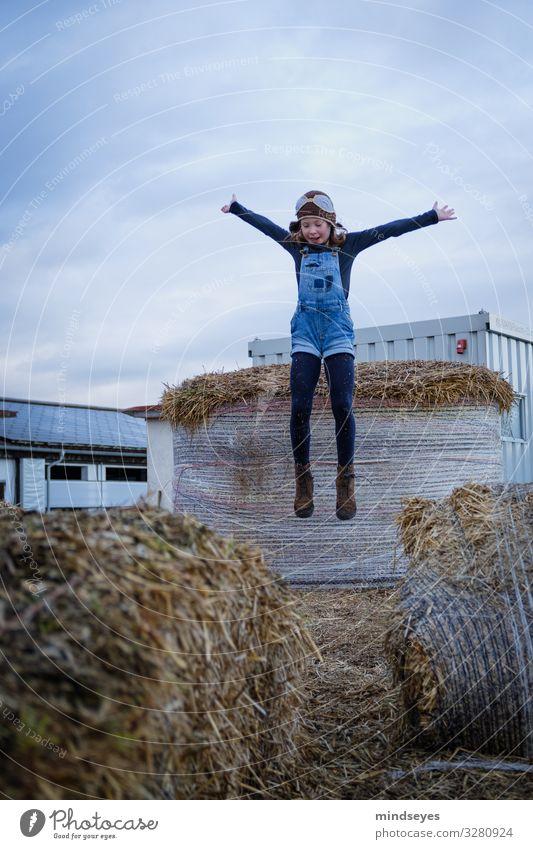 Mädchen mit Latzhose und Fliegermütze springt ins Stroh Freude Freizeit & Hobby Spielen Abenteuer Kind Kindheit 1 Mensch 3-8 Jahre Wolken Strohballen Dorf