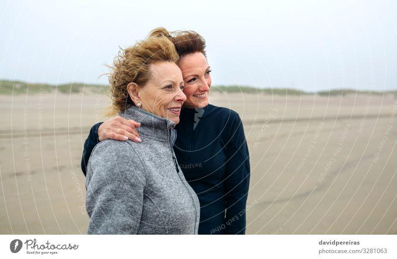 Zwei Frauen schauen im Herbst am Strand aufs Meer Lifestyle Freude Glück schön Mensch Erwachsene Mutter Großmutter Familie & Verwandtschaft Sand Wind Nebel