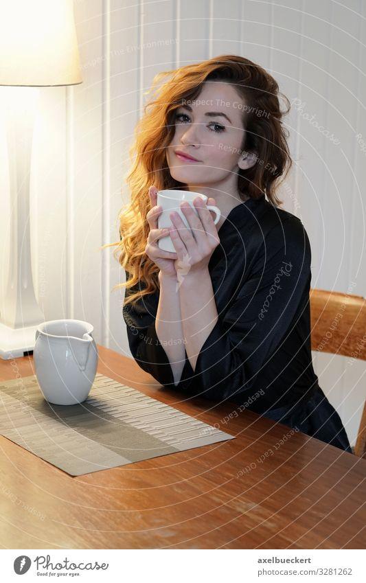 junge Frau mit Kaffee am Küchentisch Getränk trinken Heißgetränk Milch Tee Tasse Becher Lifestyle schön Wohlgefühl Zufriedenheit ruhig Freizeit & Hobby