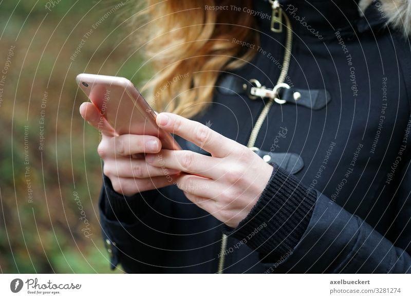 junge Frau nutzt Smartphone unterwegs Lifestyle Freizeit & Hobby Winter Telefon Handy PDA Technik & Technologie Unterhaltungselektronik Internet Mensch feminin