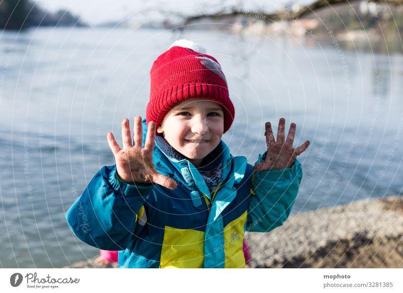 Junge mit schmutzigen Fingern am Wasser Natur bunt draußen dreck dreckig erlebnis finger hand hände jacke junge kalt kind mütze natürlich rhein rot spielen ufer