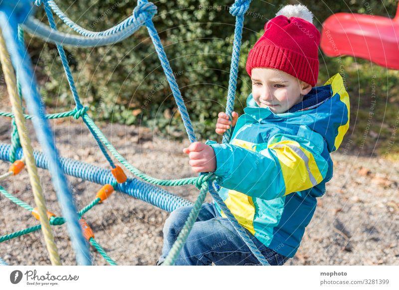 Junge auf einem Klettergerüst Kleinkind draußen drei Jahre erlebnis freude jacke junge kindheit klettergerüst klettern lachen lächeln männlich mütze sand