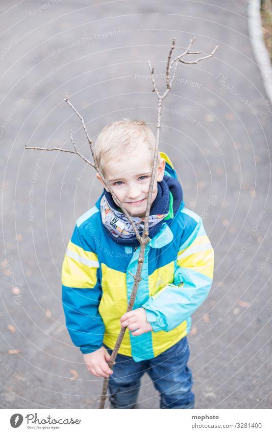 Junge mit einem Ast als Geweih Kleinkind ast draußen drei Jahre freude fröhlich geweih jacke junge kindheit kopf lachen lächeln männlich spiel spielen spielt