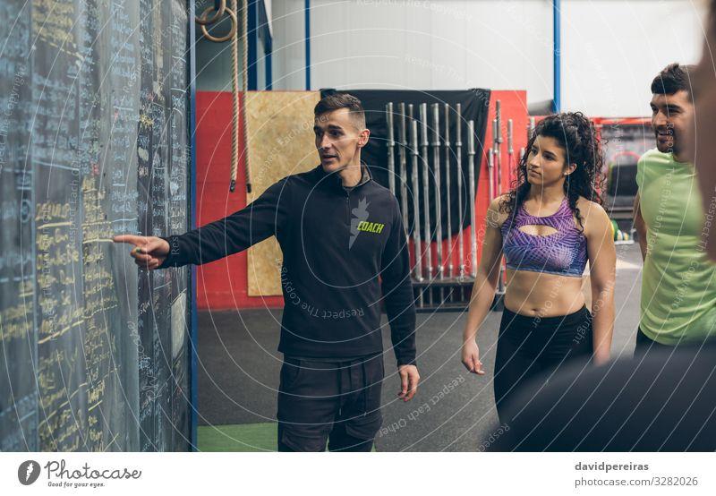 Der Trainer erklärt den Athleten in der Turnhalle Lifestyle Sport Tafel Mensch Frau Erwachsene Mann Menschengruppe Fitness hören sportlich authentisch Trainerin