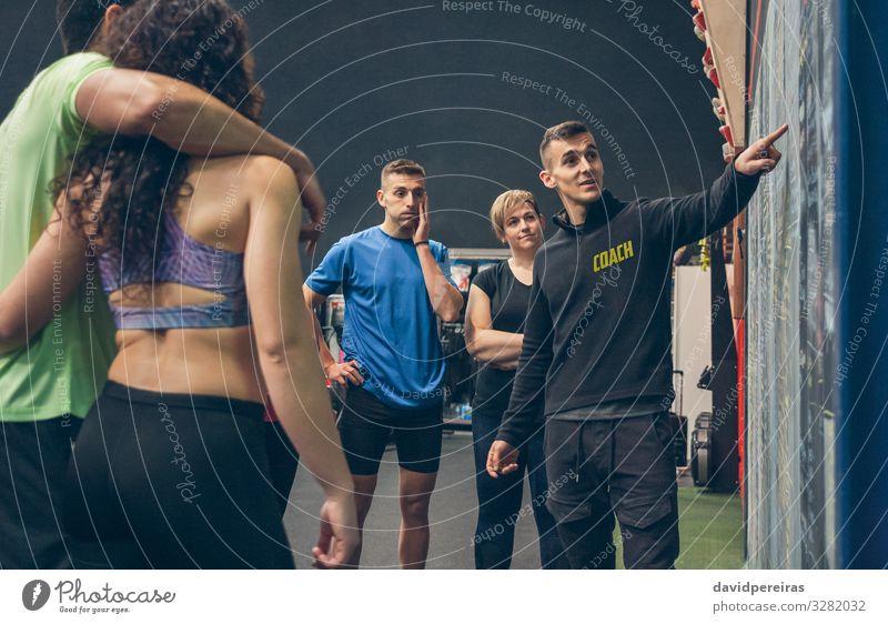 Der Trainer erklärt den Athleten in der Turnhalle Lifestyle Sport Tafel Mensch Frau Erwachsene Mann Menschengruppe Fitness hören sportlich Sporthalle erklären