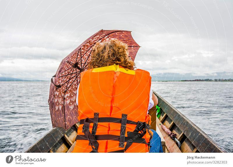 Touristin im Wassertaxi am Inle-See Wolken Wetter Regen Verkehr Taxi Sicherheit Inle See Asien Rettungsweste Regenschirm Weste Farbfoto