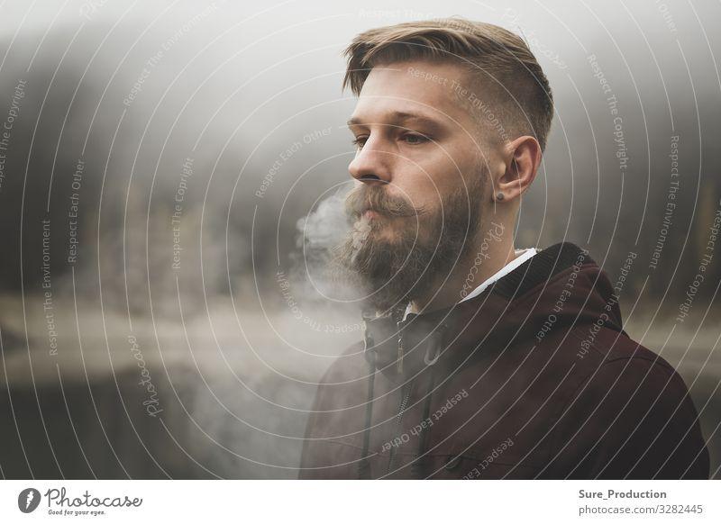 Hübscher bärtiger Mann raucht Zigarette Bläst Dampf durch die Nasenlöcher aus Rauch Erwachsener ernst Vollbart jung Kaukasier Stil stylisch Hintergrund