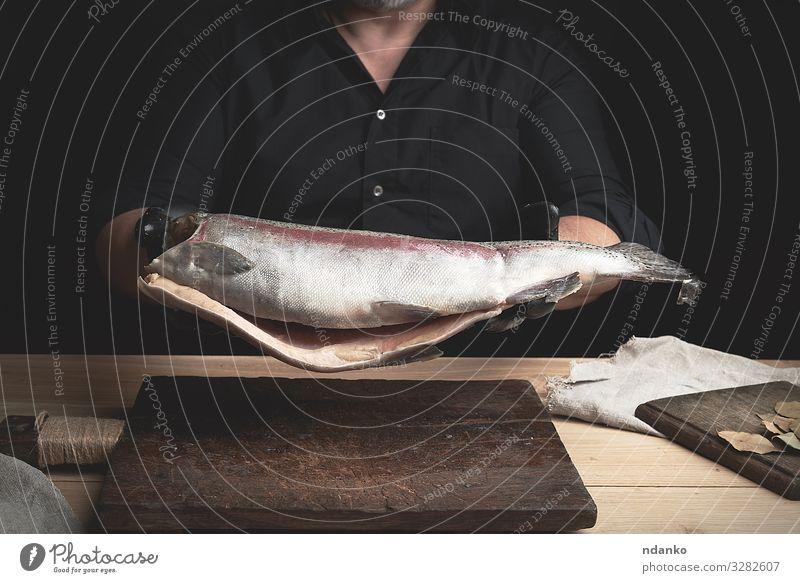 kopfloser Lachsfisch Fleisch Fisch Meeresfrüchte Ernährung Abendessen Tisch Küche Werkzeug Mann Erwachsene Hand Handschuhe Holz frisch groß braun schwarz
